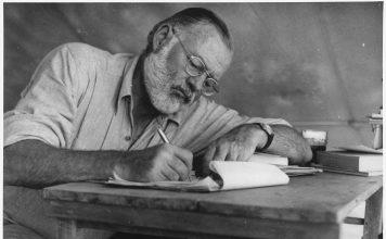 2161px Ernest Hemingway Writing at Campsite in Kenya NARA 192655 356x220 - Início